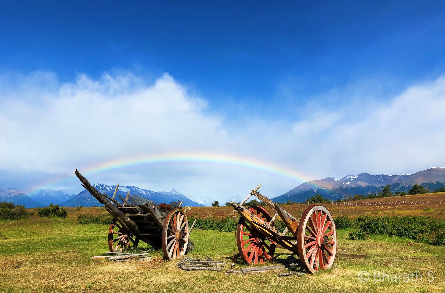 A rainbow over two carts in a field
